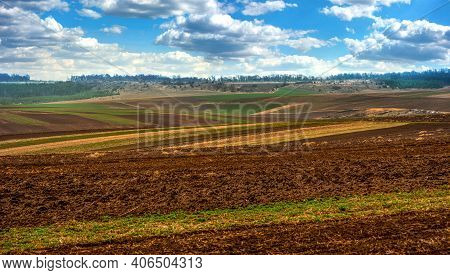arable fields stretching to horizon under blue sky with clouds on distant hills. Agriculture and farming concept.