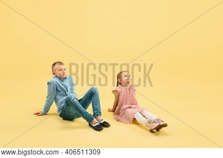 Dreamful. Childhood And Dream About Big And Famous Future. Pretty Boy And Girl Isolated On Yellow St
