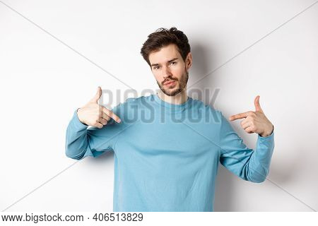 Young Man With Beard Feeling Confident, Pointing At Himself And Making Smug Face, Standing On White