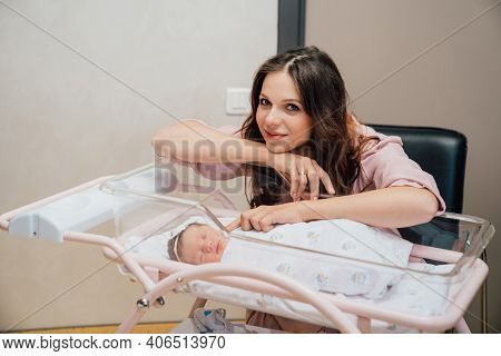 The Mother Sitting By The Newborn Baby In The Cradle