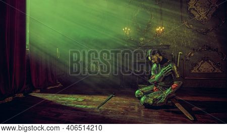 The noble knight in armor sits in the castle with his head bowed before the sword. Romance.
