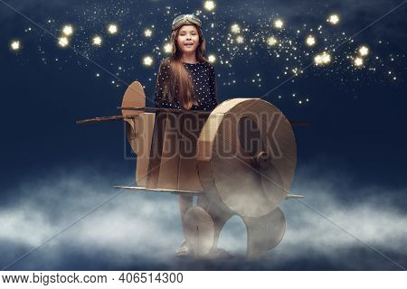 Happy dreamer girl playing with a cardboard airplane. Childhood. Fantasy, imagination. Studio portrait on a dark blue background with stars.
