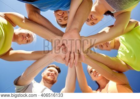 fitness, sport and healthy lifestyle concept - group of happy sporty friends stacking hands outdoors