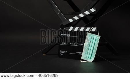 Black Director Chair With Clapperboard Or Movie Clapper Board And Face Mask On Black Background.it U