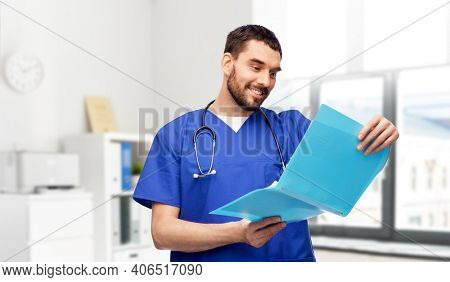 healthcare, profession and medicine concept - happy smiling doctor or male nurse in blue uniform reading medical report in folder over medical office at hospital on background