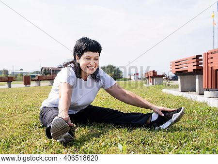 Smiling Senior Woman Warming Up Stretching Sitting On The Grass In The Park