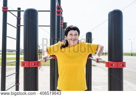 Smiling Senior Woman Doing Reverse Push Ups Outdoors On The Sports Ground Bars