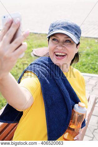 Smiling Senior Sportswoman Doing Selfie Outdoors In The Park