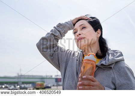 Senior Woman Wiping Out Sweat After Hard Workout Outdoors In The Park