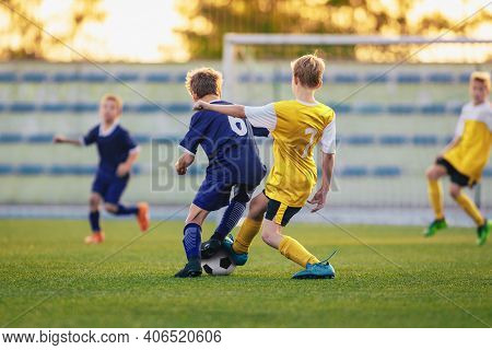 Children Playing Football. Group Of Young Boys Kicking Soccer Ball On Stadium Field. Players Compete