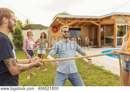 Group Of Cheerful Young Friends Having Fun At Summertime Outdoor Party By The Swimming Pool, Partici