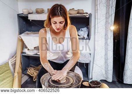 Potter Woman, Sculptor, With A Sculpting Tool, Creatively Shapes A Piece Of Wet Clay With A Potter's