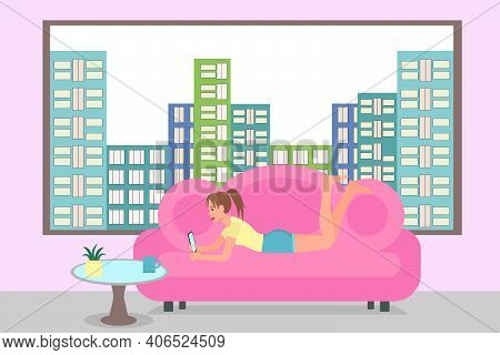 The Girl Lies On The Couch With A Phone In Her Hand Against The Background Of The City. Beautiful Vi