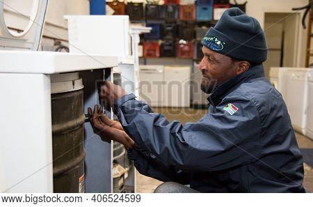 African Technical Serviceman Repairing A Broken Washing Machine