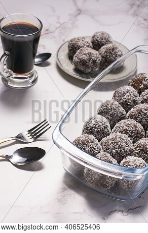 Oats Bonbons With A Coffee , A Spoon And A Fork In A White Table.