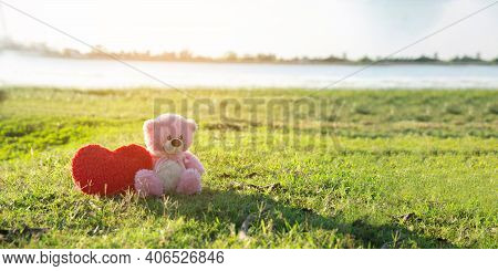 Teddy Bear With Love Red Heart,toy Sitting On Green Grass With Sunrise Background.a Red Heart Lovely