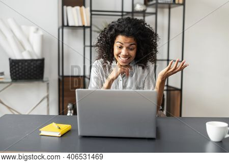 Surprised African-american Female Freelancer Office Worker With Afro Hairstyle Sitting At The Desk,