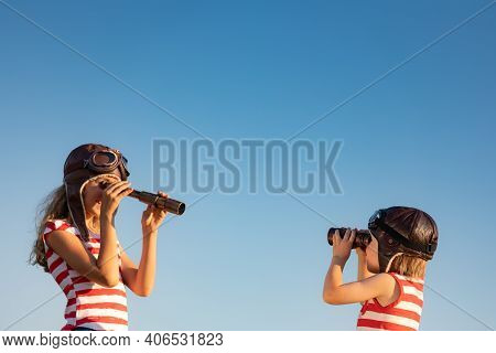 Children Playing Against Summer Sky Background. Kids Having Fun Outdoor. Summer Vacation And Travel