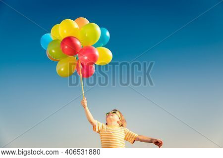 Happy Child Playing With Bright Multicolor Balloons Outdoor. Kid Having Fun In Green Spring Field Ag