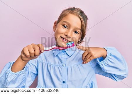 Little beautiful girl holding toothbrush with toothpaste smiling happy pointing with hand and finger