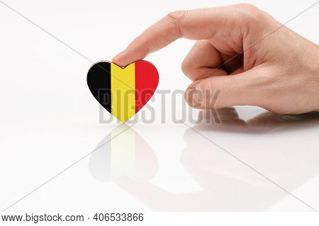 Love And Respect Belgium. A Man's Hand Holds A Heart In The Shape Of The Belgian Flag On A White Gla