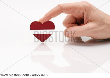 Love And Respect Latvia. A Man's Hand Holds A Heart In The Shape Of The Latvian Flag On A White Glas