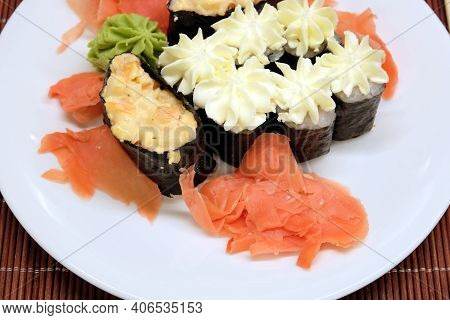 Still-life With Appetizing Sushi Pieces On The White Plate On Brown Wicker Straw Mat Top View Close