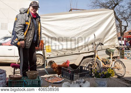 Sombor, Serbia - March 19, 2016: Senior Old Man Selling Farm Products, Food, On A Stall, Holding A L