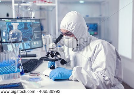 Healthcare Specialist Analyzing Vaccine On Microscope Dressed In Protection Suit. Virolog In Coveral