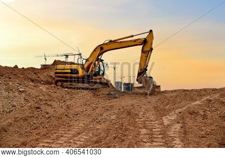 Excavator Digs Dirt During Roadwork At Construction Site. Heavy Machinery And Earth-moving Equipment