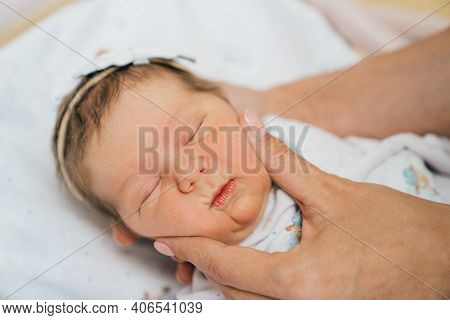 Moms Hands And A Newborn Girl With A White Band On Her Head Sleeps In A Cradle