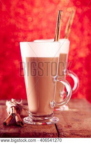 coffee latte with cinnamon sticks, red glitter backdrop, shallow dof