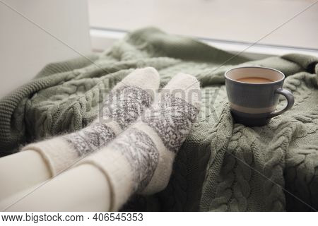Woman Wearing Warm Socks On Knitted Plaid Near Window, Closeup. Cozy Season