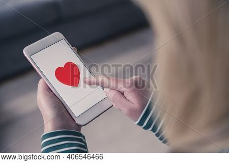 A Girl Tapping The Touchscreen Of Her Mobile Phone To Like And Find Love With An Online Dating App