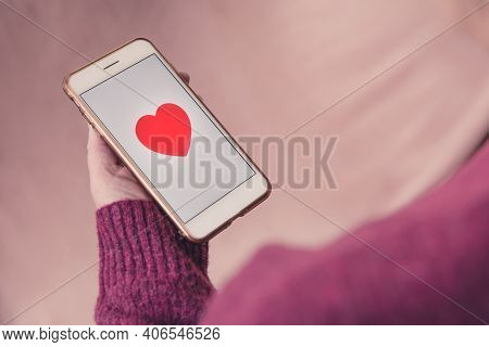 A Girl Tapping A Love Heart Emoji On The Touchscreen Of Her Mobile Phone To Like And Find Love With