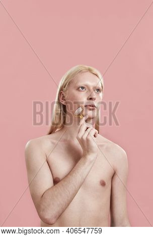 Young Caucasian Man With Long Blond Hair Massaging Face Using Quartz Roller While Standing On Pink B