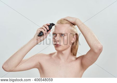 Young Caucasian Blond Man With Long Hair Using Hair Trimmer On Forehead While Standing On Light Back