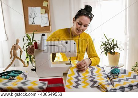 Woman Sewing On A Sewing Machine At Her Home. Woman Seamstress Work On The Sewing-machine