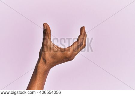 Arm and hand of black middle age woman over pink isolated background picking and taking invisible thing, holding object with fingers showing space
