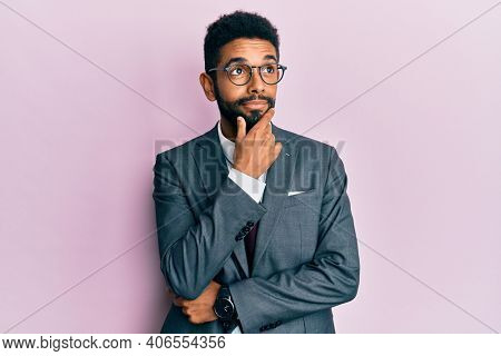 Handsome hispanic business man with beard wearing business suit and tie with hand on chin thinking about question, pensive expression. smiling with thoughtful face. doubt concept.