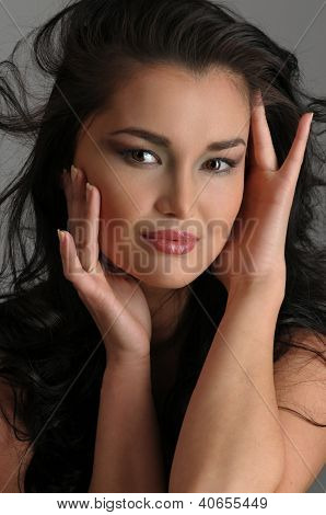 Portrait of sexy Asian brunette at isolated grey studio background