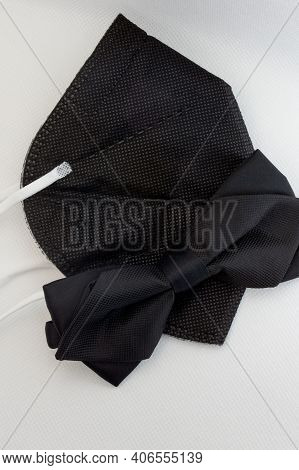 A new concept of style required for adapting to the times of coronavirus. Black bow tie and a black respirator. For everyday life or as an elegant wedding kit for a groom.