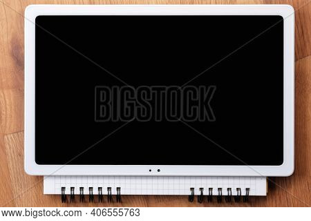 On An Open Tear-off Notebook For Notes, Sheets Of Paper In A Box, Lies A Switched Off Tablet With A