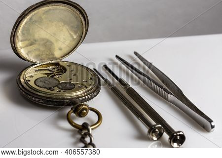 Antiques, Vintage Swiss Pocket Watch, Two Screwdrivers And Tweezers Lie On A White Plastic Table
