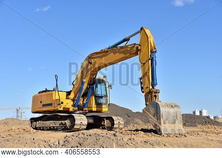 Excavator On Earthworks At Construction Site. Backhoe On Foundation Work And Road Construction. Heav