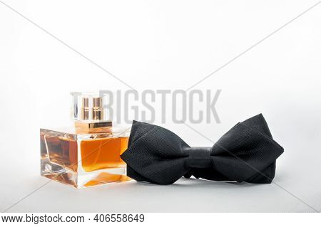 A rectangular glass bottle of brown men\\\'s perfume and a bow tie on a black and white background