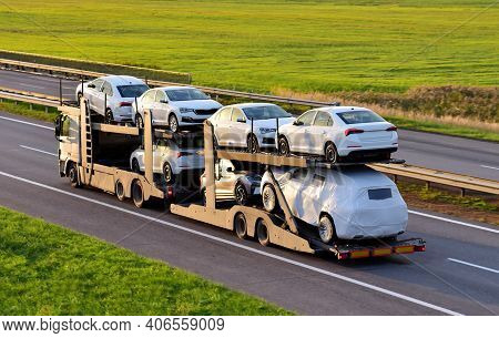 Car Carrier Trailer Transports Cars On Highway On Sunset Background. Auto Transport And Car Shipping