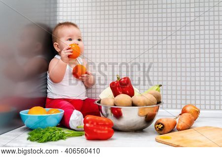 A Little Kid Sits Surrounded By Fruits And Vegetables, Holding Tomatoes In His Hands. The Concept Of