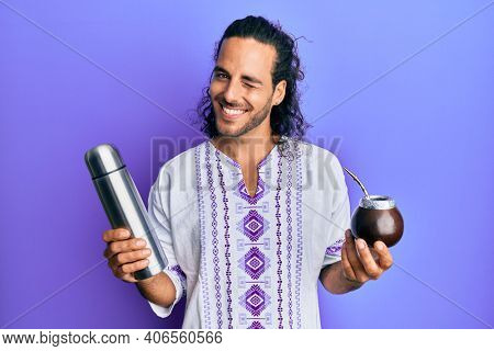 Young handsome man with long hair drinking mate infusion winking looking at the camera with sexy expression, cheerful and happy face.