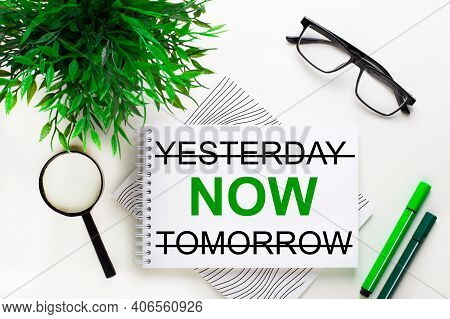 On A White Background Lies A Notebook With The Word Yesterday Now Tomorrow, Glasses, A Magnifying Gl